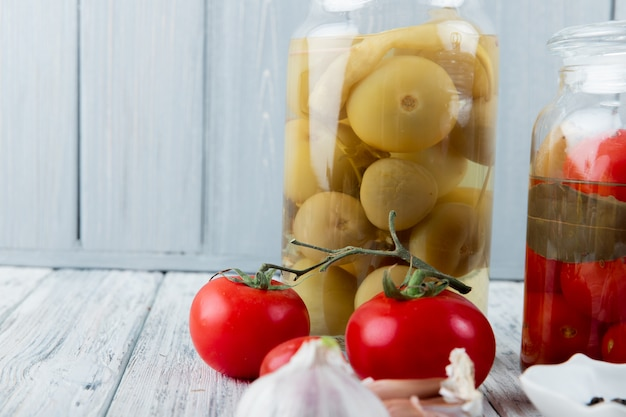 Sluit omhoog mening van zure groene en rode tomaten op houten oppervlakte en achtergrond met exemplaarruimte