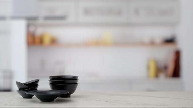 Sluit omhoog mening van zwarte ceramische kommen die op marmeren lijst met vage keukenruimte worden gestapeld