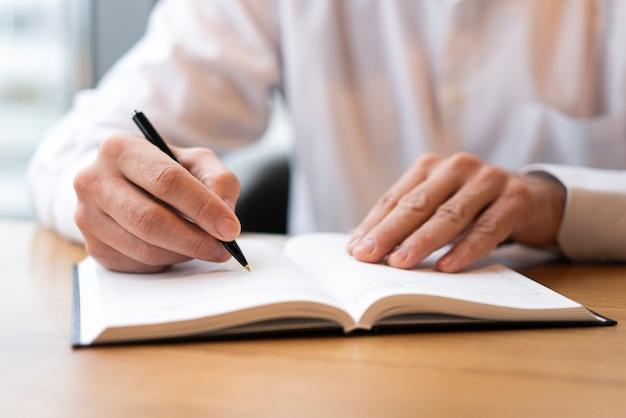 Sluit omhoog mens die in agenda schrijven