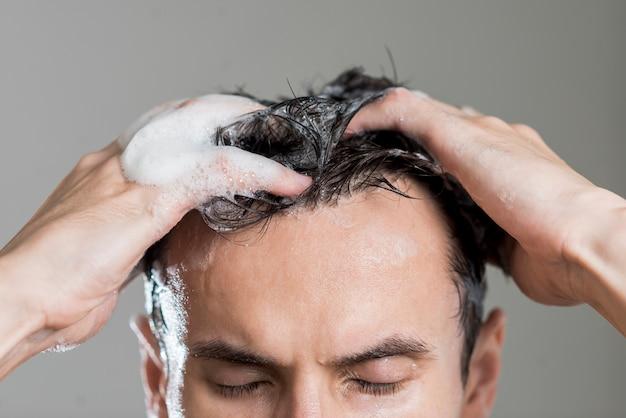 Sluit omhoog mens die zijn haar wast