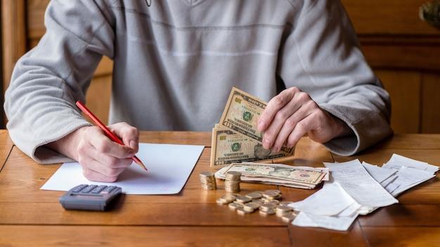 Sluit omhoog mens met calculator tellen, thuis nota's makend, is de hand geschreven in een notitieboekje. gestapelde munten gerangschikt in deesk. besparingen financiën concept.