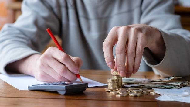 Sluit omhoog mens met calculator tellen, thuis nota's makend, is de hand geschreven in een notitieboekje