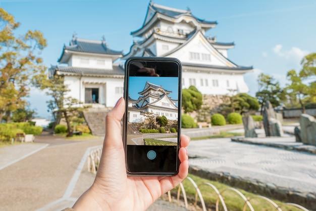 Sluit omhoog menselijke hand is foto kishiwada-kasteel in kishiwada-stad, osaka