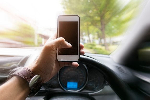 Sluit omhoog mensenhand gebruikend slimme telefoon terwijl hij de auto drijft