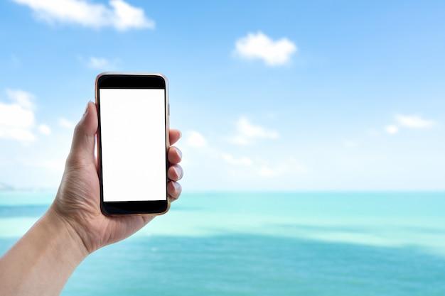 Sluit omhoog mensenhand houdend zwarte smartphone op mooie kalme blauwe overzees en witte hemelachtergrond.