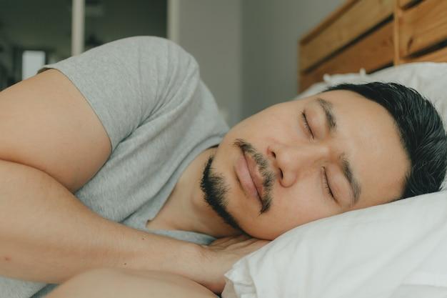 Sluit omhoog mensenslaap op zijn bed met gelukkig gezicht. concept van een goede nachtrust.