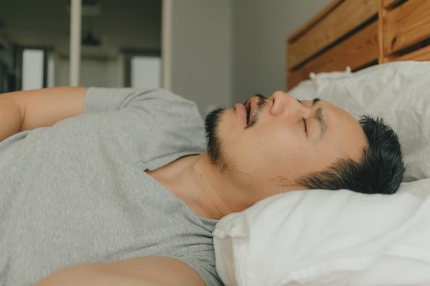 Sluit omhoog mensenslaap op zijn bed met snurkgezicht