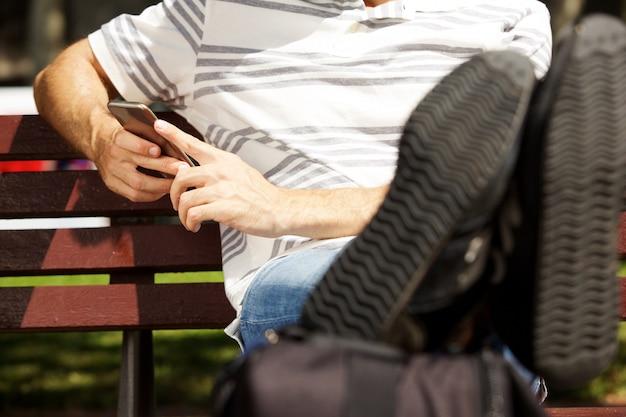 Sluit omhoog mensenzitting op bank in openlucht met benen op zak en het gebruiken van mobiele telefoon