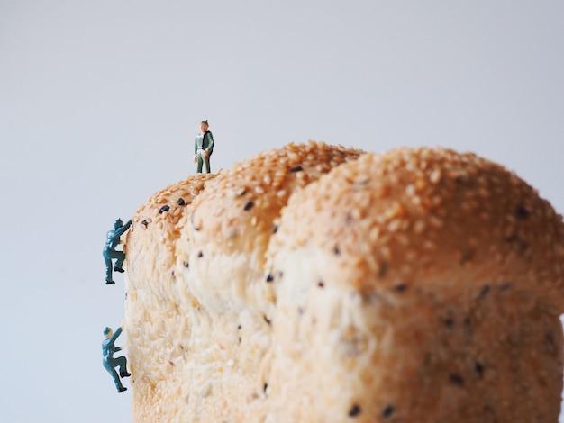 Sluit omhoog miniatuurmensen veel van de arbeidersmens die aan de gehele achtergrond van het korrelbrood werken