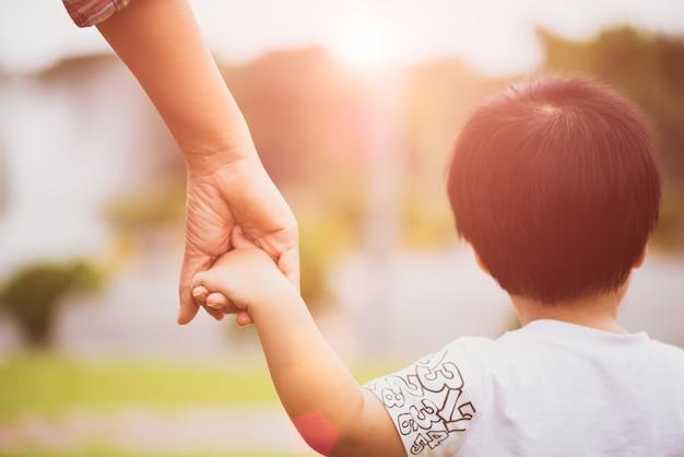 Sluit omhoog moeder die de hand van een kind houden. familie en moeders dag concept.
