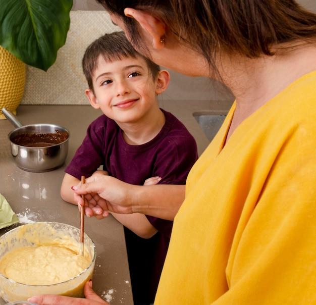 Sluit omhoog moeder en jongen die samen koken