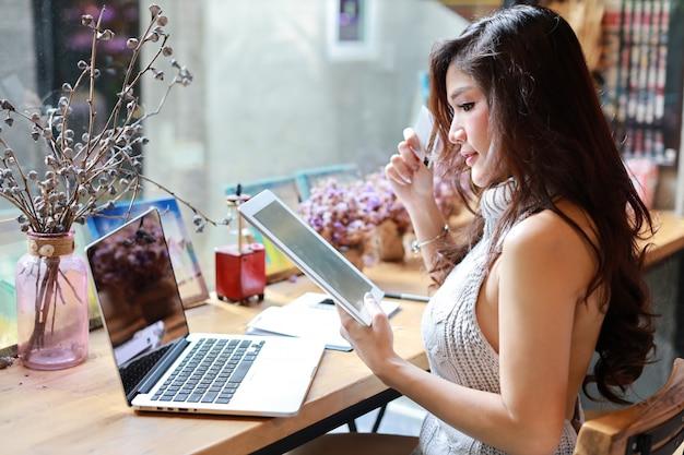 Sluit omhoog mooie en aantrekkelijke aziatische vrouw, lang haar in grijze toevallige kleding die aan tablet werken