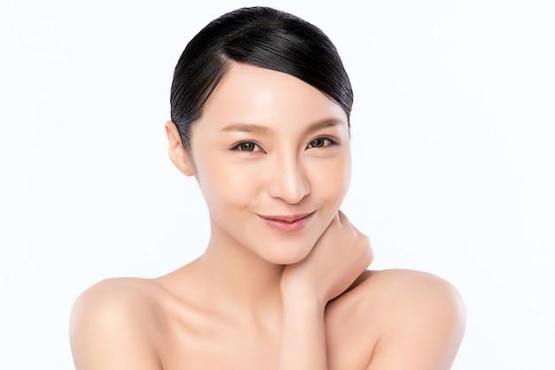 Sluit omhoog mooie jonge aziatische vrouw wat betreft haar schoon gezicht met verse gezonde geïsoleerde huid, schoonheidsschoonheidsmiddelen en gezichtsbehandelingsconcept