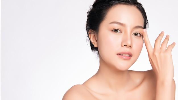 Sluit omhoog mooie jonge aziatische vrouw wat betreft haar schoon gezicht met verse gezonde huid, schoonheidsschoonheidsmiddelen en gezichtsbehandelingsconcept