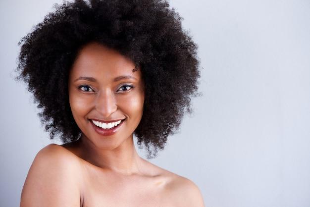 Sluit omhoog mooie jonge vrouw die met naakte schouders op grijze achtergrond glimlachen