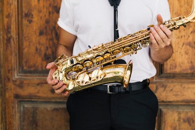 Sluit omhoog musicus die de saxofoon houdt