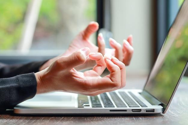 Sluit omhoog onderneemsterhand gevoel uitgeput van teveel gebruikend computer