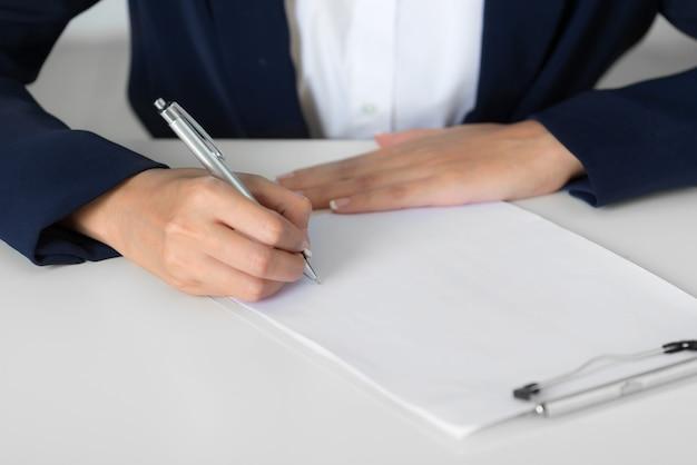 Sluit omhoog onderneemsterhanden die een kostuum dragen die op een leeg document blad neerschrijven