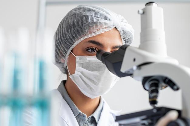 Sluit omhoog onderzoeker die met microscoop werkt