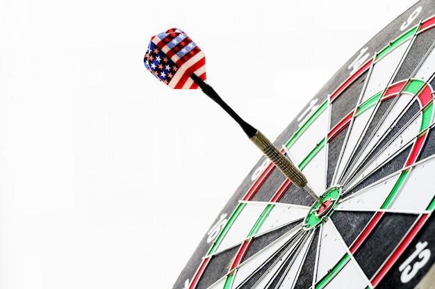 Sluit omhoog ontsproten van de pijltjepijl die op bulleyes van dartboard wordt geraakt. doel en doel als concept.
