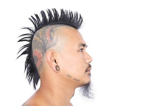 Sluit omhoog ontsproten van het hoofd van de aziatische punker met de stijl van het mohawkhaar, tatoegering op hoofd en oor geïsoleerde doordringen