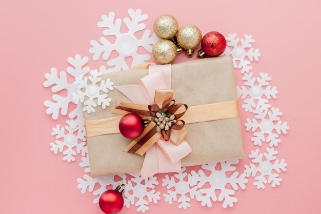 Sluit omhoog ontsproten van kleine gift die met lint op roze wordt verpakt. kerstmis. minimaal . plat leggen. bovenaanzicht