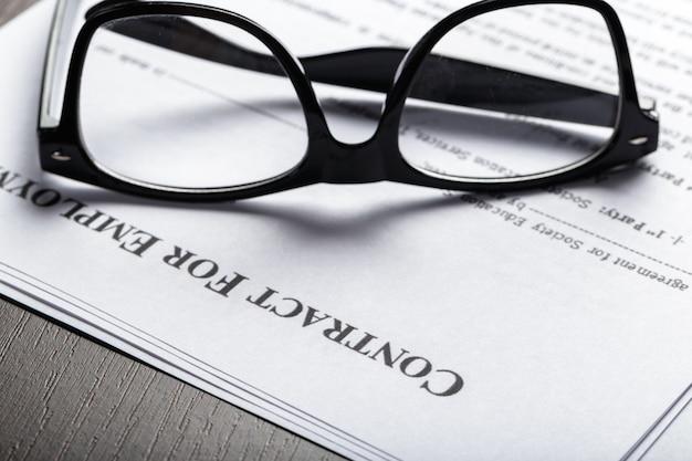 Sluit omhoog ontsproten van oogglazen op de documenten van het contractdocument bedrijfsconcept