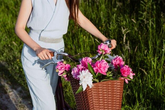 Sluit omhoog ontsproten van vrouwelijke handen, houdt zij een fiets met een mand van rode en witte pioenenbloemen.