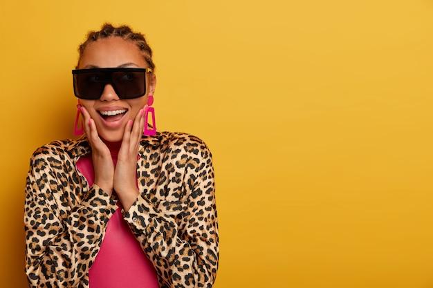Sluit omhoog op aantrekkelijke onbezorgde jonge vrouw die zonnebril draagt
