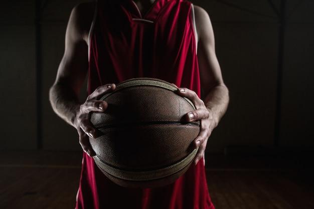 Sluit omhoog op basketbalspeler die een bal houdt