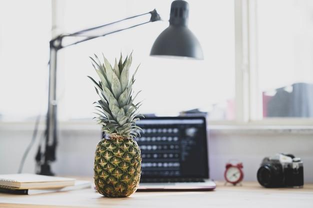 Sluit omhoog op bureau in het bureau met ananas