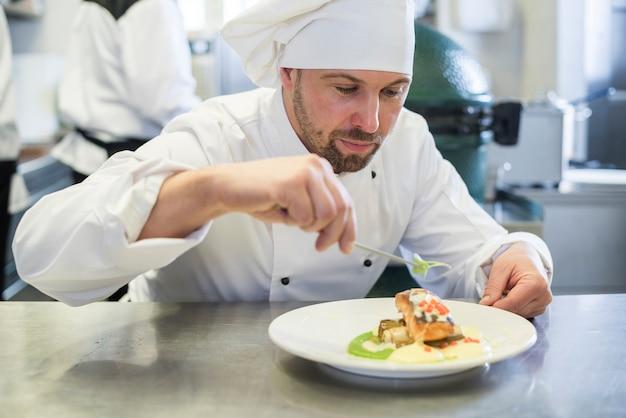 Sluit omhoog op chef-kok die de schotel na het koken verfraait