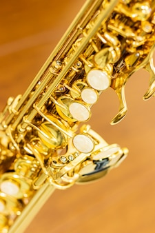 Sluit omhoog op de details van de sopraansaxofoon, vage achtergrond