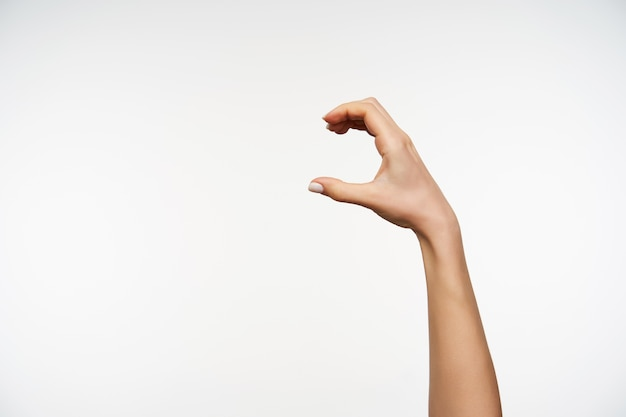 Sluit omhoog op de hand van de jonge vrouw iets met vingers gebaren