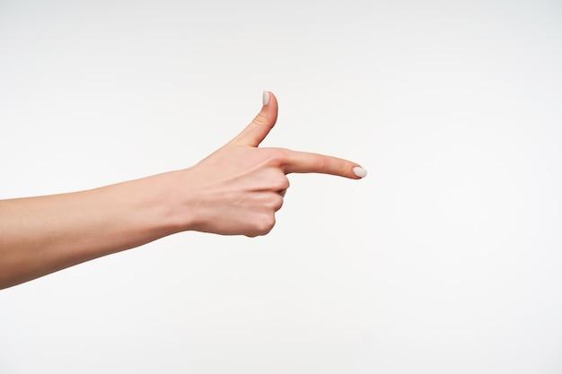 Sluit omhoog op de hand van de jonge vrouw met witte manicure die wordt verhoogd