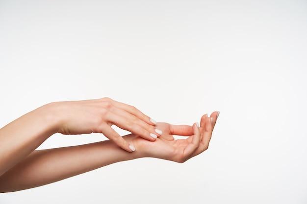 Sluit omhoog op de hand van de mooie jonge opgeheven vrouw met witte manicure