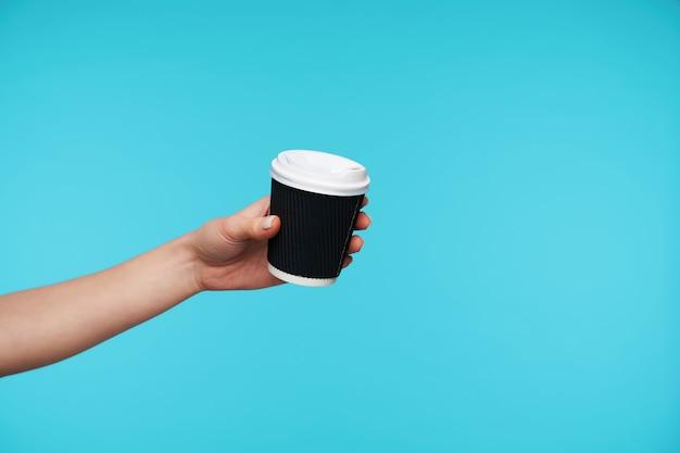 Sluit omhoog op de handen die worden opgeheven terwijl u een kopje koffie omhoog houdt
