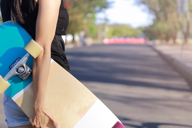 Sluit omhoog op de holdingskateboard van de jonge vrouwenhand, surfschaats