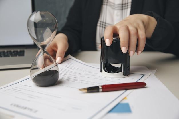 Sluit omhoog op de notarishand van de vrouw die het document stempelt. notaris concept.