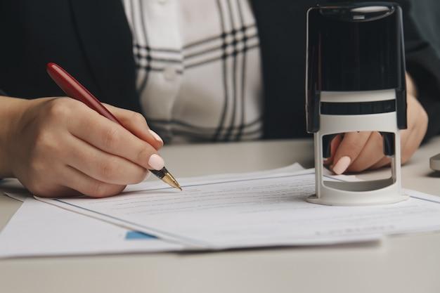 Sluit omhoog op de notarishand van de vrouw die het document stempelt
