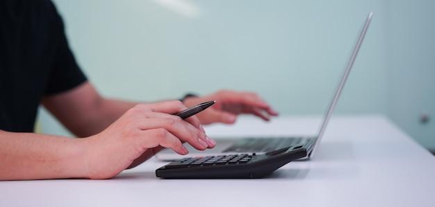 Sluit omhoog op de vingerpers van de werknemersmens op calculator voor leid uitgavenconcept