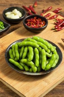 Sluit omhoog op edamame-bonen in een kom met rode spaanse pepers