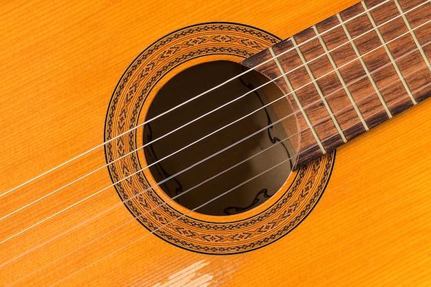 Sluit omhoog op een klassieke gitaar die van hout wordt gemaakt.