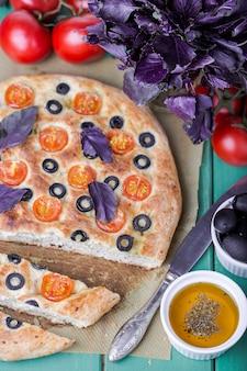 Sluit omhoog op focaccia met tomaten, zwarte olijven en basilicum