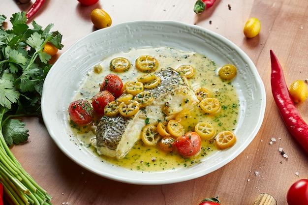 Sluit omhoog op gastronomische gegrilde filet van snoekbaars met gele saus en groenten in witte kom op houten oppervlakte in samenstelling met ingrediënten