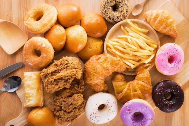 Sluit omhoog op geassorteerde ongezonde kost en bestek