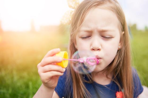 Sluit omhoog op gelukkig jong geitje dat met zeepbellen speelt