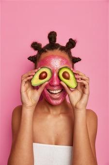 Sluit omhoog op gelukkige etnische vrouw geniet van het toepassen van geïsoleerd gezichtsmasker Gratis Foto