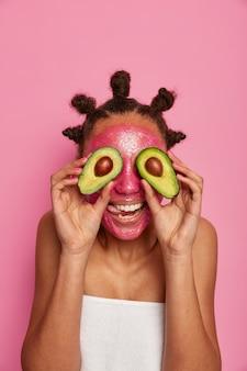 Sluit omhoog op gelukkige etnische vrouw geniet van het toepassen van geïsoleerd gezichtsmasker