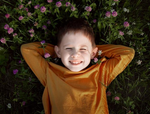 Sluit omhoog op glimlachende jongen die op het gras ligt